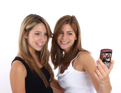 Två tjejer tar självporträtt med hjälp av mobilen